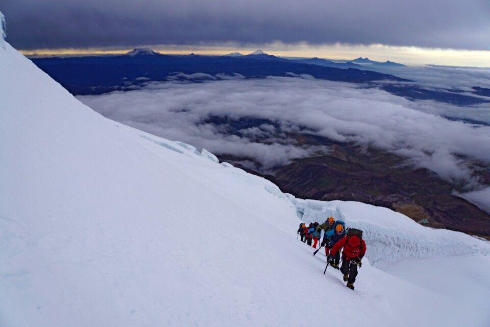 Aufstieg am Cayambe über den Gletscher. Am Horizont die Eisgipfel, Antisana, Chimborazo und Cotopaxi (v.l.).