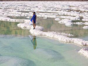 Frau, die auf dem Salz im Toten Meer geht