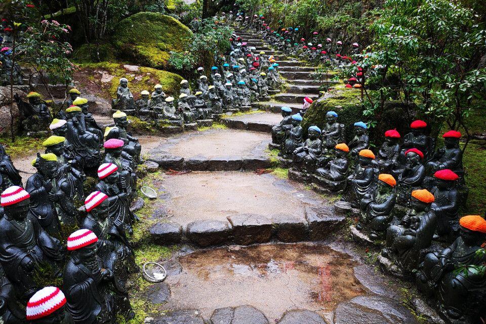Zahlreiche kleine Skulpturen mit gehäkelten Mützen säumen pittoresk den Weg in einer Schreinanlage